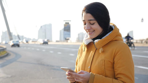 Beautiful girl writes a message on a smartphone. Slow motion. Roadway on the Footage