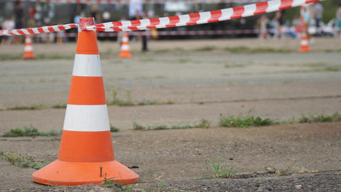 Fencing tape and road cone on the background of passing people Footage