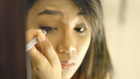 Young Thai Woman Applying eyeliner Footage
