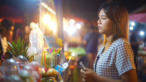 Young Woman buying juice in night market Stock Video Footage