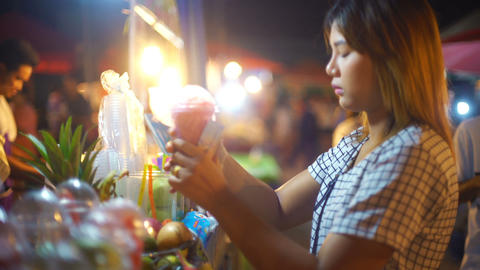 Young Woman buying juice in night market Footage