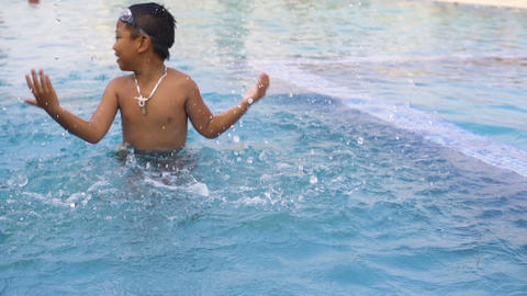 Little boy playing in outdoor swimming pool slowmotion Footage