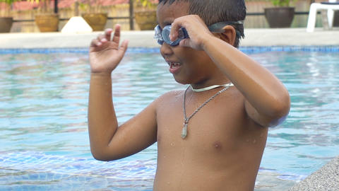 Little boy wearing goggles and diving in swimming pool slowmotion Footage