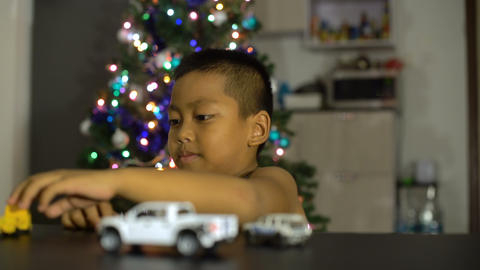 Little asian boy having fun with gift toy cars Footage