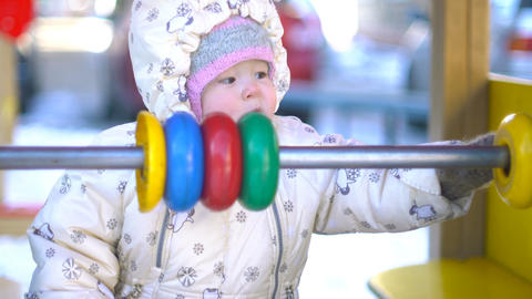 Baby girl playing with multicolor abacus in winter Footage