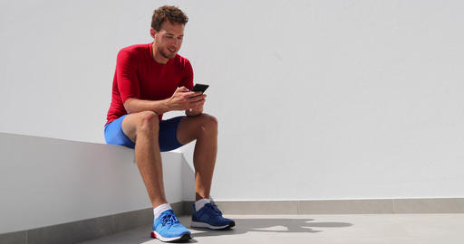 Athlete man texting looking at phone screen at home after working out training Footage