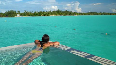 Seamless Loop video: Sexy bikini body woman relaxing swimming in luxury pool Footage