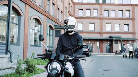 Young man and biker in helmets on motorcycle in city with urban background Footage