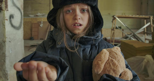 Little homeless Caucasian girl in dirty winter clothes holding the teddy bear Live Action