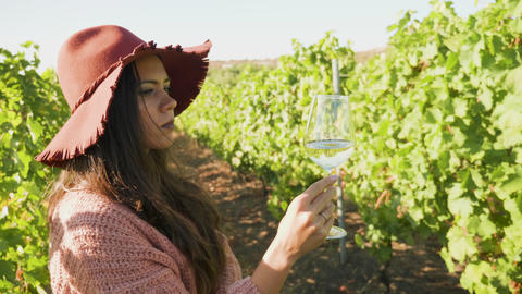 Woman in a vineyard looking at a glass of wine GIF