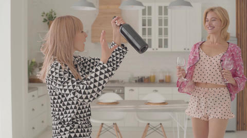 Two beautiful blonde Caucasian women dancing with a bottle of wine and two Live Action