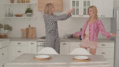 Two beautiful blonde Caucasian girls dancing at the kitchen. Girls in having Live Action