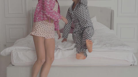 Two cheerful blonde Caucasian girls jumping at the white bed and laughing Footage