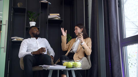 Pleasant joyful multiracial male and female office managers drinking coffee at Live Action