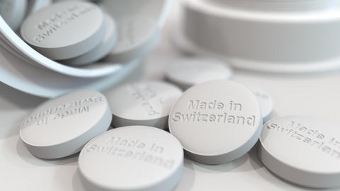 Pills with MADE IN SWITZERLAND text on them. National pharmaceutical industry Live Action
