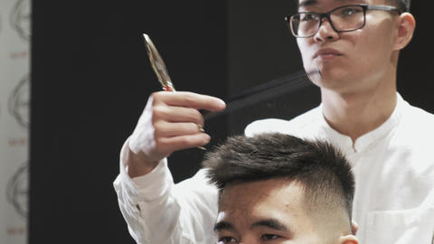 Asian hairdresser in glasses combing hair to client in salon Live Action