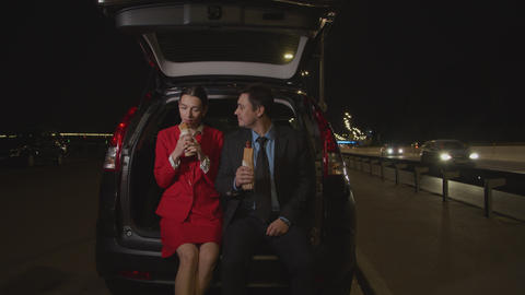 Couple on road trip enjoying fast food at night Live Action