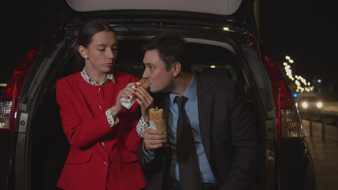 Business colleagues sharing meal in car at night Live Action