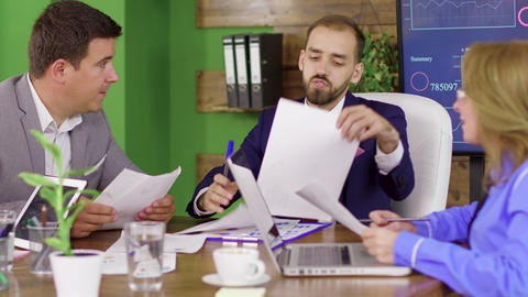 Bearded team leader in business suit having a meeting with his investment team Live Action