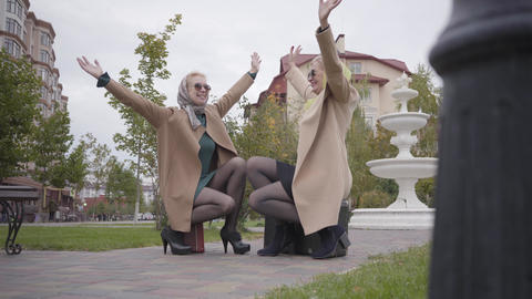 Two adult Caucasian women in squatting position raising hands up and smiling Footage