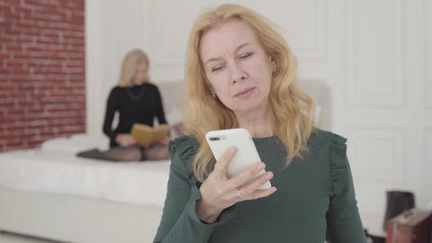 Portrait of an attractive Caucasian mature woman talking by the phone at home Footage
