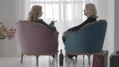 Back view of mature blonde Caucasian women sitting in comfortable armchairs and ビデオ