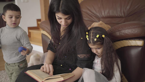 Pretty Middle Eastern woman reading the book to little children. Mother Footage