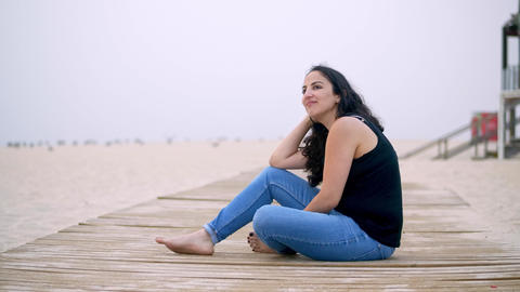 Young woman sits on a wooden pier at the beach Footage