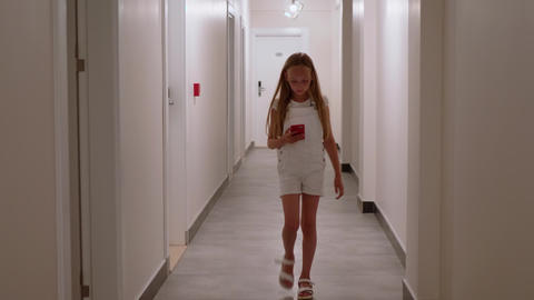 Young girl walking on hotel corridor with mobile phone. Teenager girl using Live Action