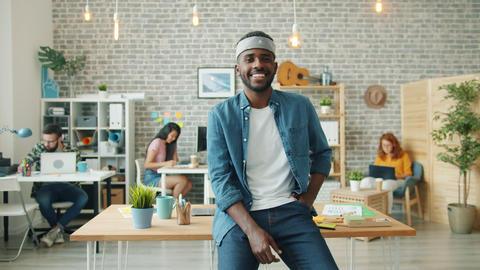 Slow motion portrait of joyful African American businessman smiling in office Footage