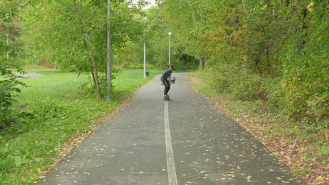 Teenager boy riding on longboard at pathway in summer park. Young boy Live Action