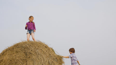 Carefree teenagers playing on haystack on countryside field in village. Happy Footage