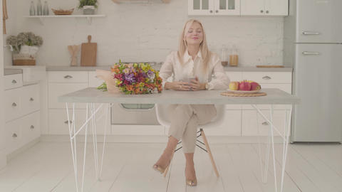 Blond Caucasian lady sitting at the table with a cup of tea or coffee and a Footage