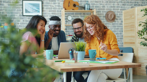 Men and women multi-racial team using laptop in office talking laughing Live Action