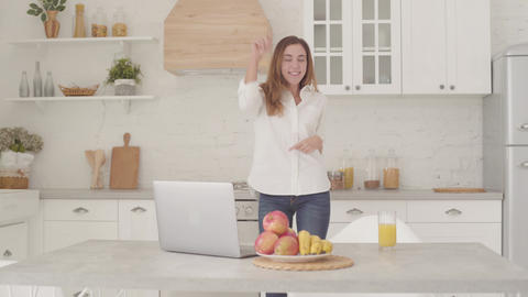 Cheerful Caucasian girl in casual clothes dancing in the light modern kitchen Footage