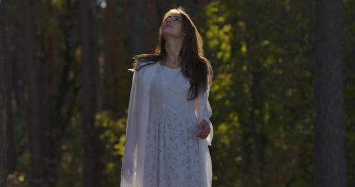 Cute Caucasian girl standing in sunlight in the forest and looking up. Beautiful Footage