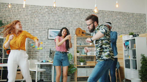 Bearded guy dancing in office while coworkers clapping hands having fun together Footage