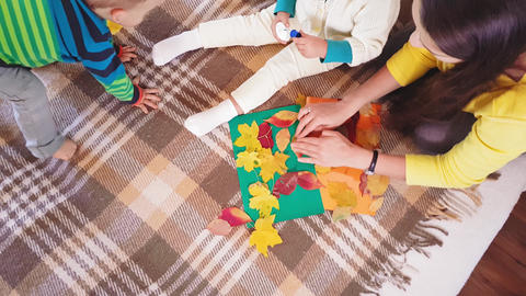Young mother with children make autumn applique from autumn leaves. Little girl Footage