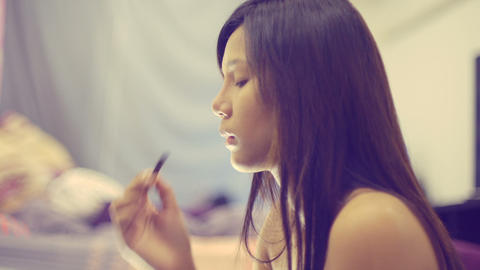 Young Asian Woman looking in mirror and applying cosmetics Footage