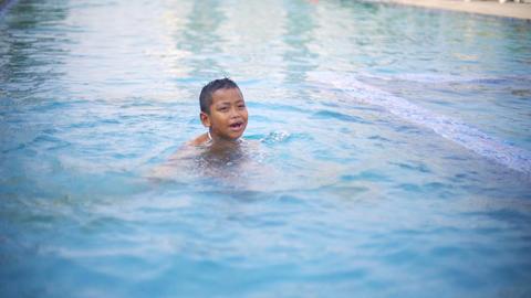 Little boy having fun in outdoor swimming pool slowmotion Footage