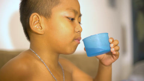 Little Thai boy drinking water Footage