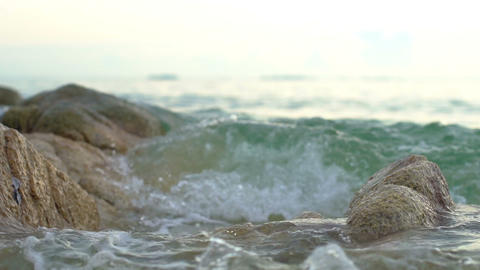 Waves crashing on stones in sea slowmotion close-up Footage