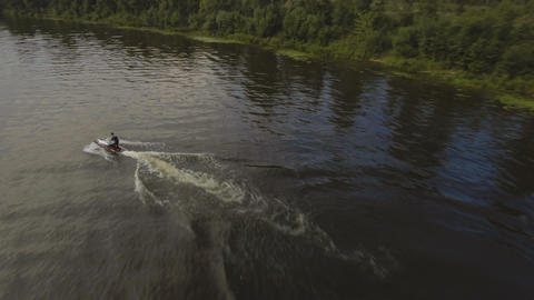 Teen boy on the jet ski in the river.Aerial video Footage