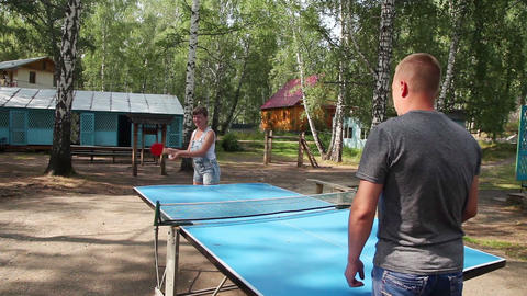 Boy and girl playing table tennis outdoors Footage