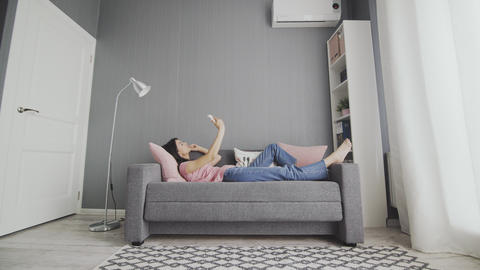 Attractive young woman typing on her smart phone while lying on the sofa at home Footage