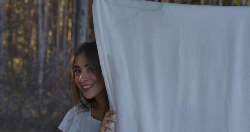 Young Caucasian positive girl hiding behind white clothing in the forest Footage