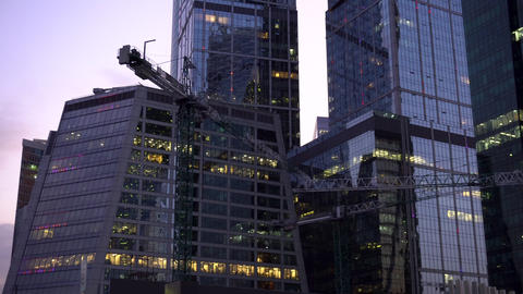 Construction cranes stand next to the skyscrapers.… Stock Video Footage