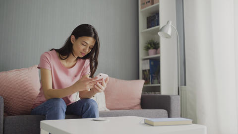 Young Woman Scrolling her Smartphone. Young woman scrolls the social media feed ライブ動画