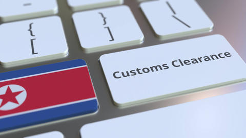 CUSTOMS CLEARANCE text and flag of North Korea on the computer keyboard. Import Live Action