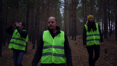 group of volunteers in green vests went in search of missing persons in a pine Live Action